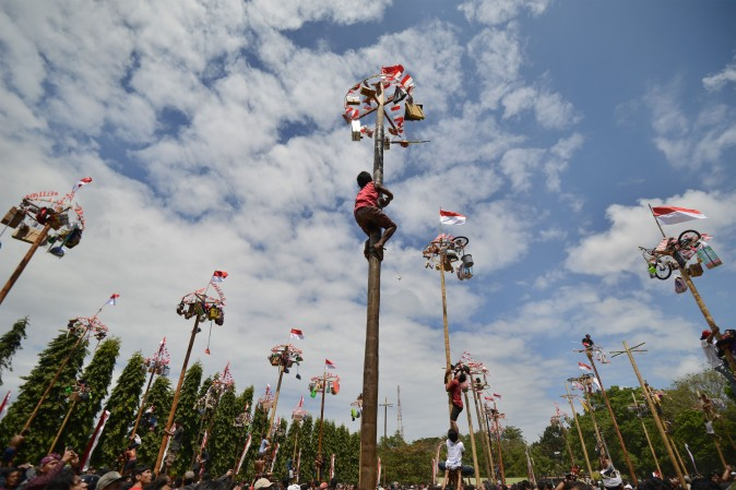 People climb greased poles, on which prizes and flags are attached, to celebrate Indonesia's Independence Day in Denpasar, Indonesia, on Aug. 17, 2017. Indonesia marked the 72nd anniversary of its independence from Dutch rule on August 17. (SONNY TUMBELAKA/AFP/Getty Images)