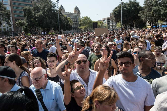 People gesture as they leave Placa de Catalunya after observing a one minute's silence for the victims of yesterday's terrorist attack, on August 18, 2017 in Barcelona, Spain. (Carl Court/Getty Images)