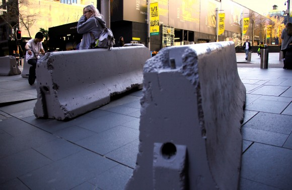 A woman rests on a concrete block that was placed by authorities as extra security measures at Sydney's Martin Place in Australia, July 18, 2017. (Reuters/David Gray)