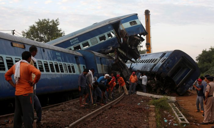 Railway workers repair the tracks next to derailed coaches of a passenger train at the site of an accident in Khatauli, in the northern state of Uttar Pradesh, India August 20, 2017. (Reuters/Adnan Abidi)