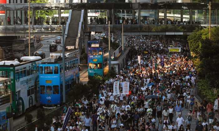 """Demonstrators march in protest of the jailing of student leaders Joshua Wong, Nathan Law and Alex Chow, who were imprisoned for their participation of the 2014 pro-democracy Umbrella Movement, also known as """"Occupy Central"""" protests, in Hong Kong, China on Aug. 20, 2017. (Tyrone Siu/Reuters)"""