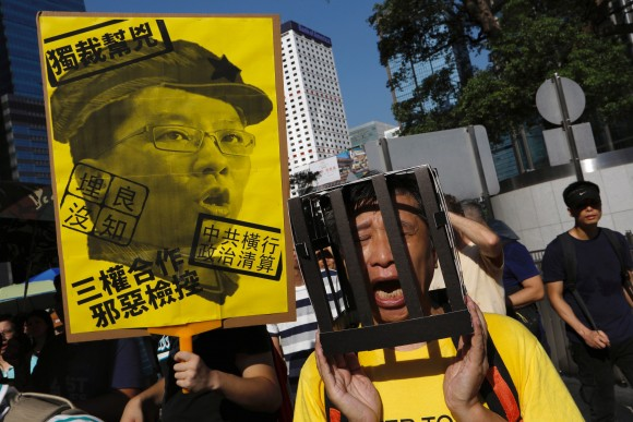 "A demonstrator holds cardboard jail bars, as he protests of the jailing of student leaders Joshua Wong, Nathan Law and Alex Chow, who were imprisoned for their participation of the 2014 pro-democracy Umbrella Movement, also known as ""Occupy Central"" protests, in Hong Kong China August 20, 2017. (Reuters/Tyrone Siu)"