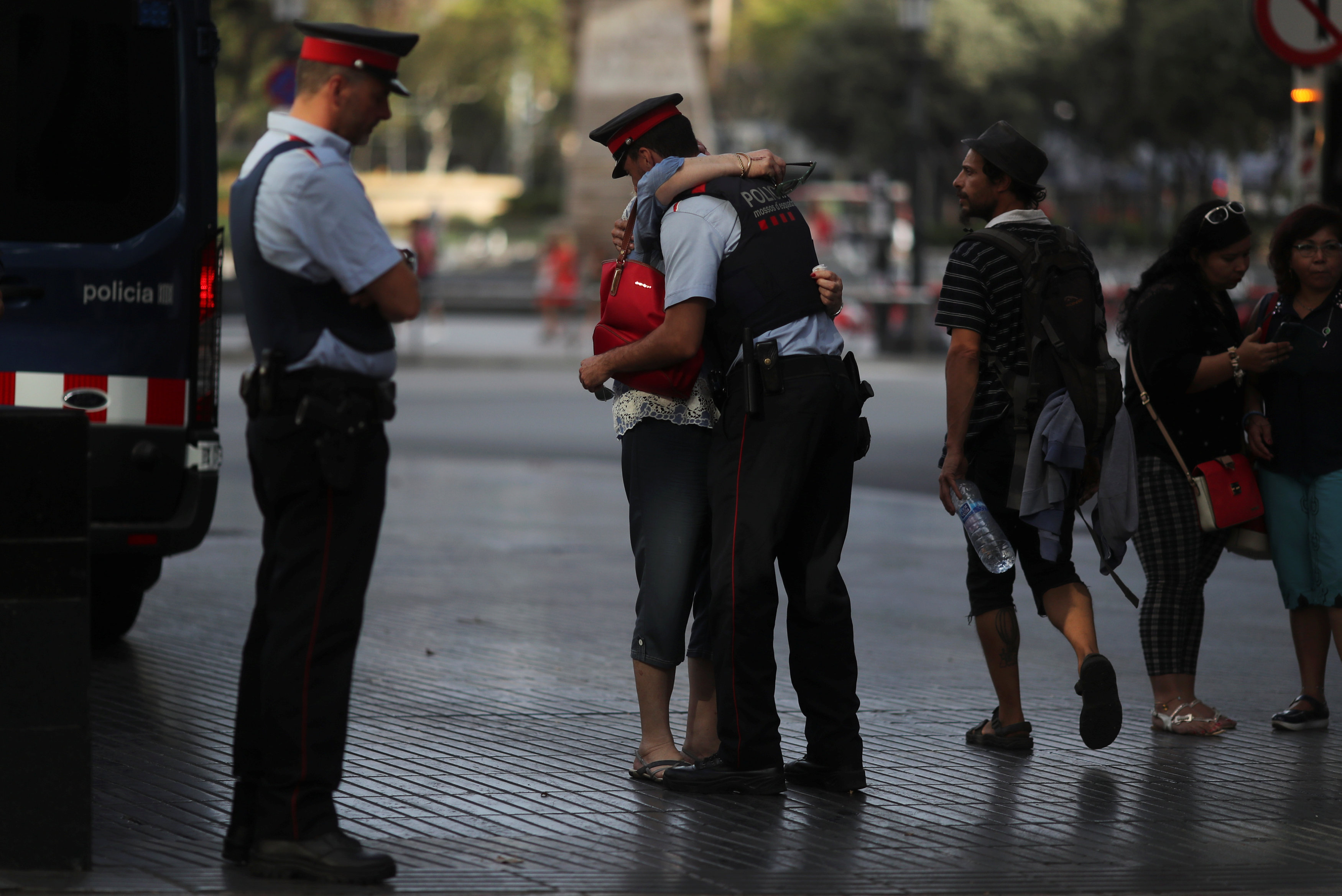 Pilar Revilla, 75, hugs a Catalan Mossos d'Esquadra officer after visiting an impromptu memorial where a van crashed into pedestrians at Las Ramblas in Barcelona, Spain on August 20, 2017. (REUTERS/Susana Vera)