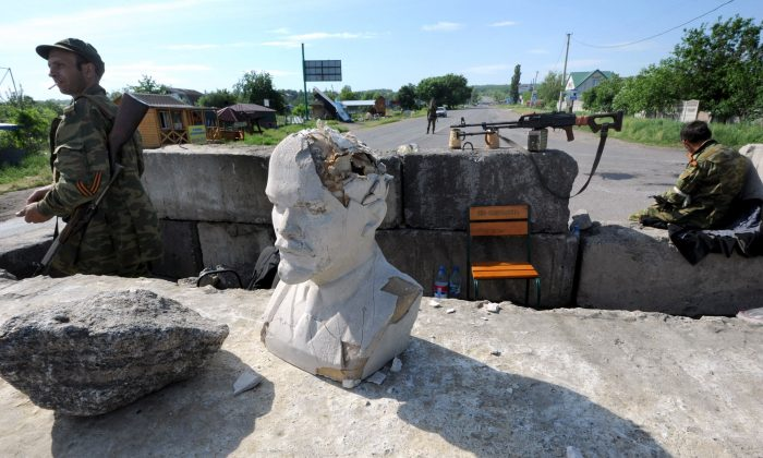 Armed pro-Russian militants guard a check-point on which is placed a bust of Lenin in the village of Semenovka, near the eastern Ukrainian city of Slavyansk, on May 22, 2014. Separatist rebels killed at least nine Ukrainian soldiers in the restive east on May 22, dealing a heavy blow to the beleaguered government just three days before a crunch presidential poll. AFP PHOTO/ VIKTOR DRACHEV        (Photo credit should read VIKTOR DRACHEV/AFP/Getty Images)