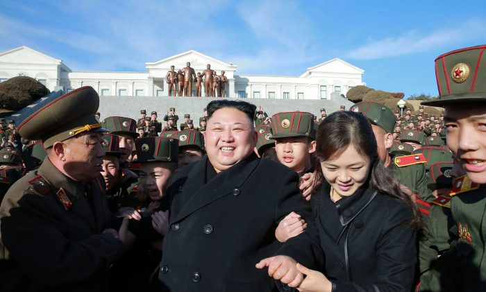This picture taken by North Korean news agency KCNA (Korean Central News Agency) on March 2, 2017 and released on March 3 shows North Korean leader Kim Jong-Un (C) and his wife Ri Sol-Ju (2nd R) visiting school in Pyongyang to plant trees with its students on a tree planting day. (STR/AFP/Getty Images)