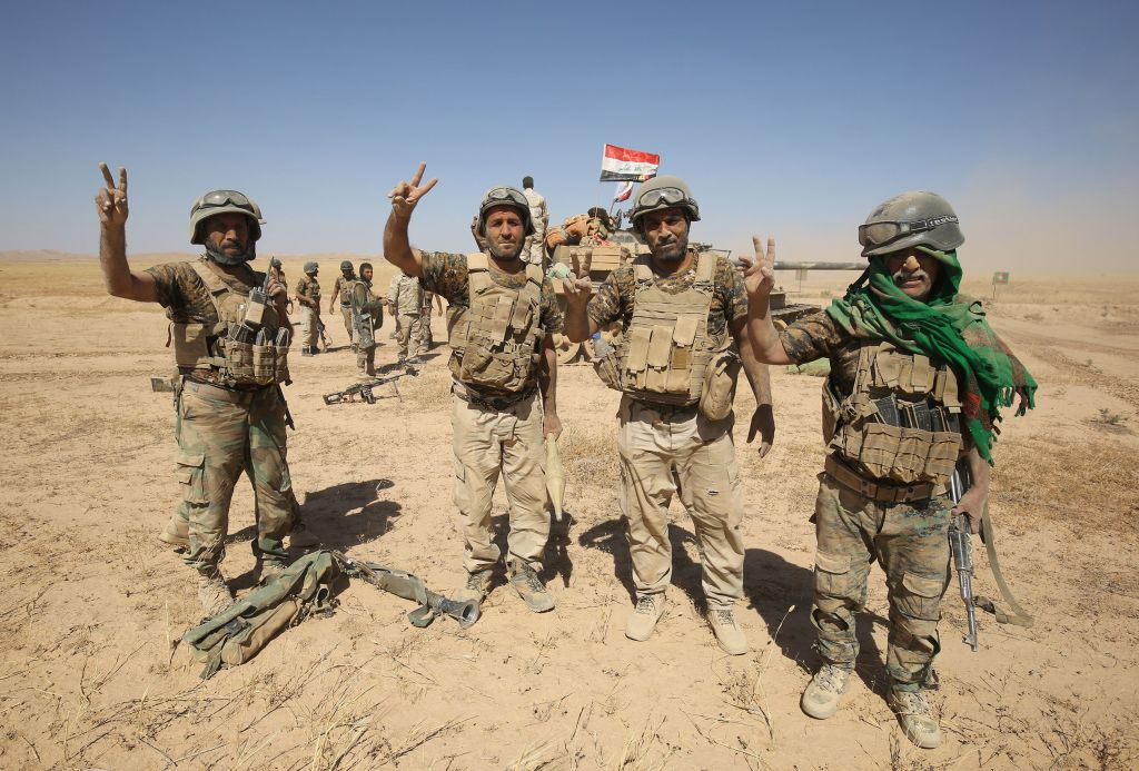 Fighters from the Hashed al-Shaabi (Popular Mobilisation) paramilitaries gesture to the camera as they prepare to advance towards the city of Tal Afar, the main remaining stronghold of the Islamic State group, after the government announced the beginning of an operation to retake it from the jihadists, on August 20, 2017. (AHMAD AL-RUBAYE/AFP/Getty Images)