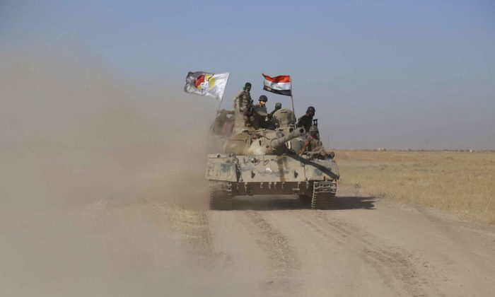 Iraqi government forces supported by fighters from the Abbas Brigade, which fights under the umbrella of the Shiite popular mobilisation units, advance towards the city of Tal Afar, the main remaining stronghold of the Islamic State group, after the government announced the beginning of an operation to retake it from the jihadists on August 20, 2017.  (MOHAMMED SAWAF/AFP/Getty Images)
