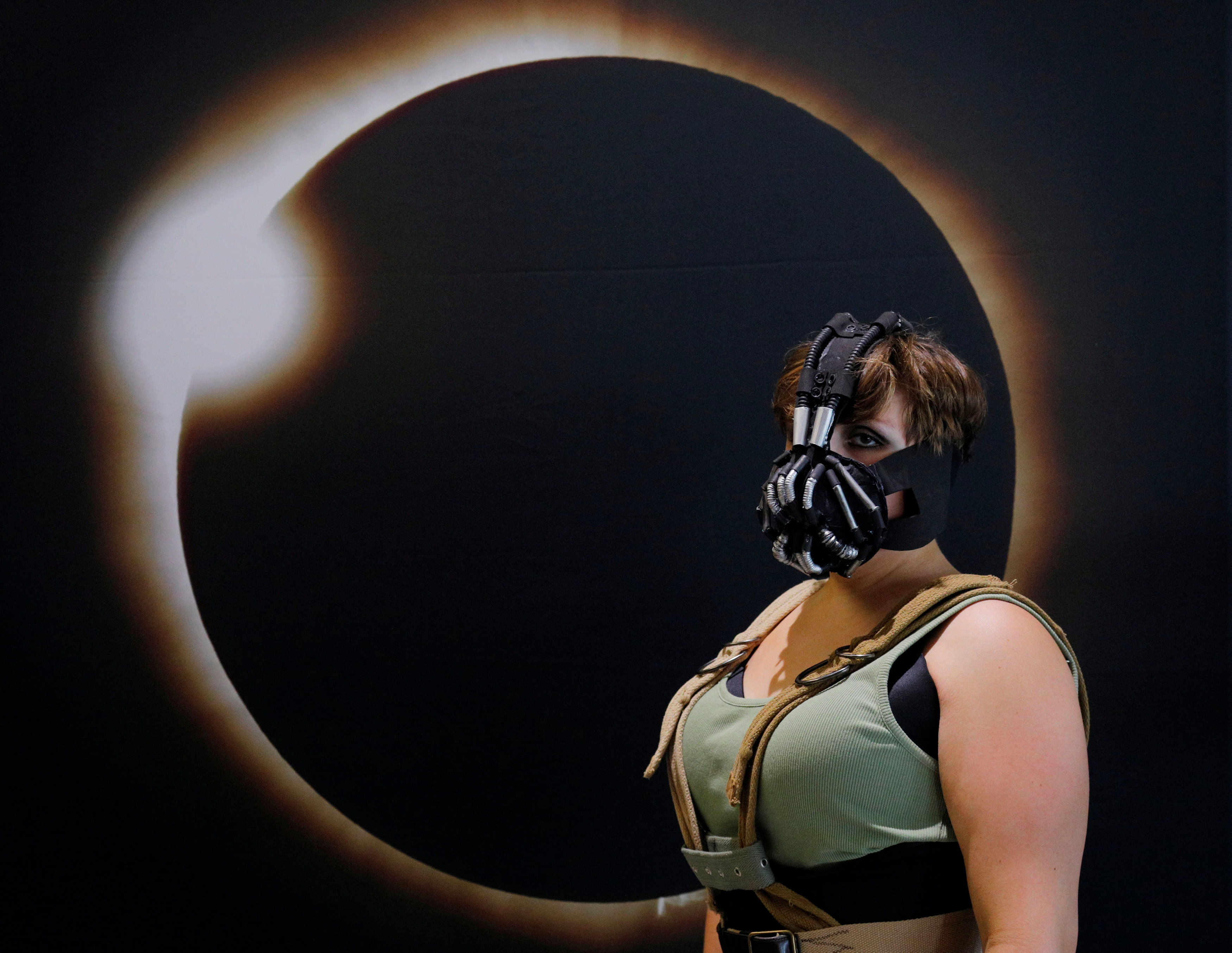Cassie Gillard, from bay City Michigan and dressed as Lady Bane from the Batman franchise, poses for a photograph in front of an image of a solar eclipse at the Eclipse Comic-Con at Southern Illinois University in Carbondale, Ill., on Aug. 20, 2017 one day before a total solar eclipse in the city.   (REUTERS/Brian Snyder)