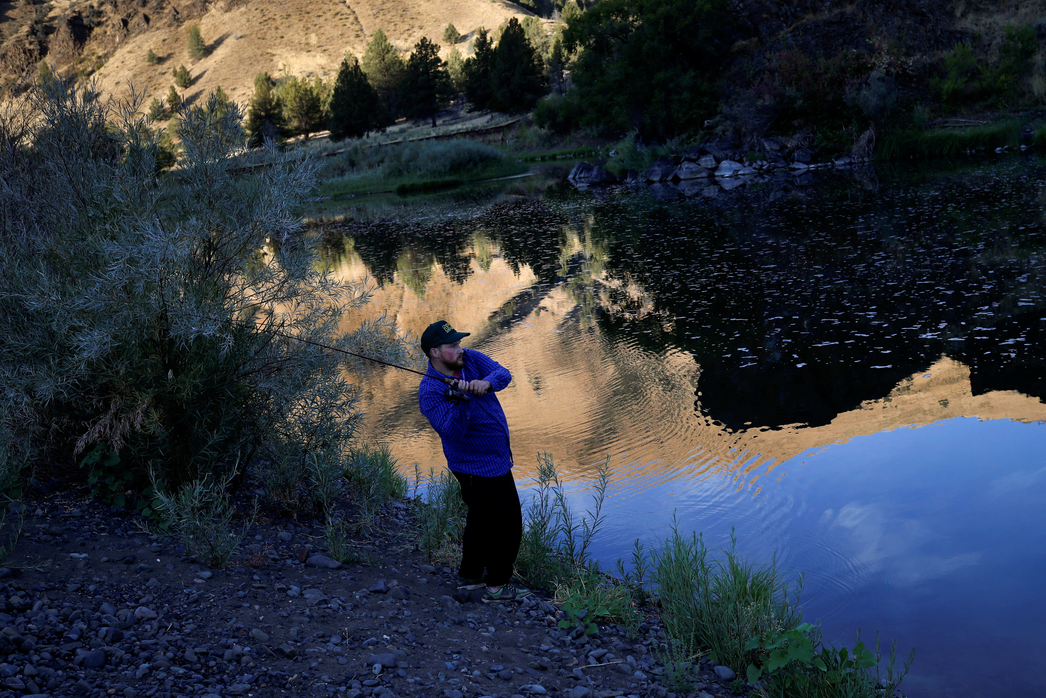 KC DeRemer fishes for bass while camping along the John Day River ahead of the total lunar eclipse in Kimberly, Oregon, U.S. August 20, 2017. REUTERS/Adrees Latif