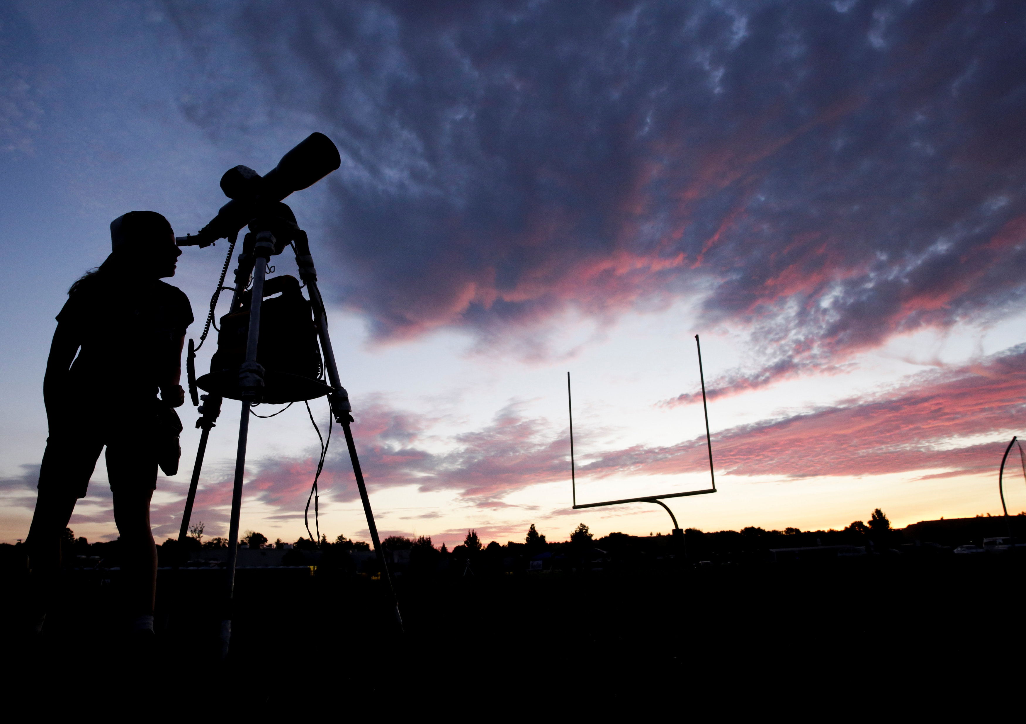 A woman looks through a telescope on the football field at Madras High School the evening before a solar eclipse in Madras, Oregon on Aug.20, 2017. (REUTERS/Jason Redmond)
