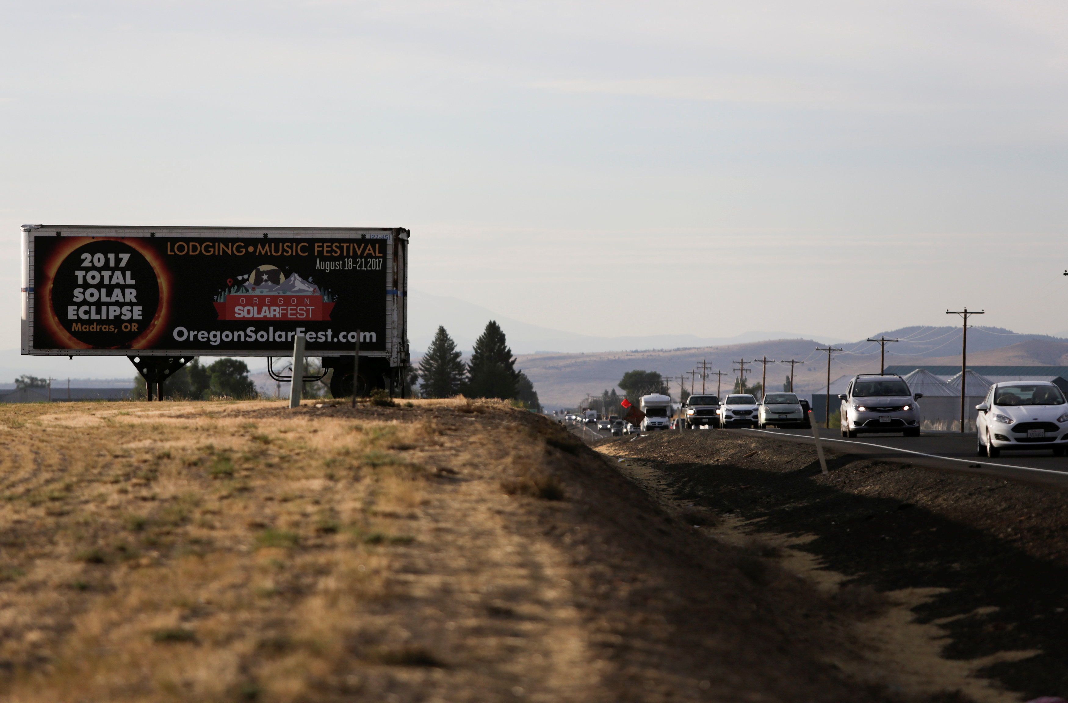 A sign promoting the solar eclipse is pictured as people drive into Madras, Oregon on Aug.20, 2017. (REUTERS/Jason Redmond)