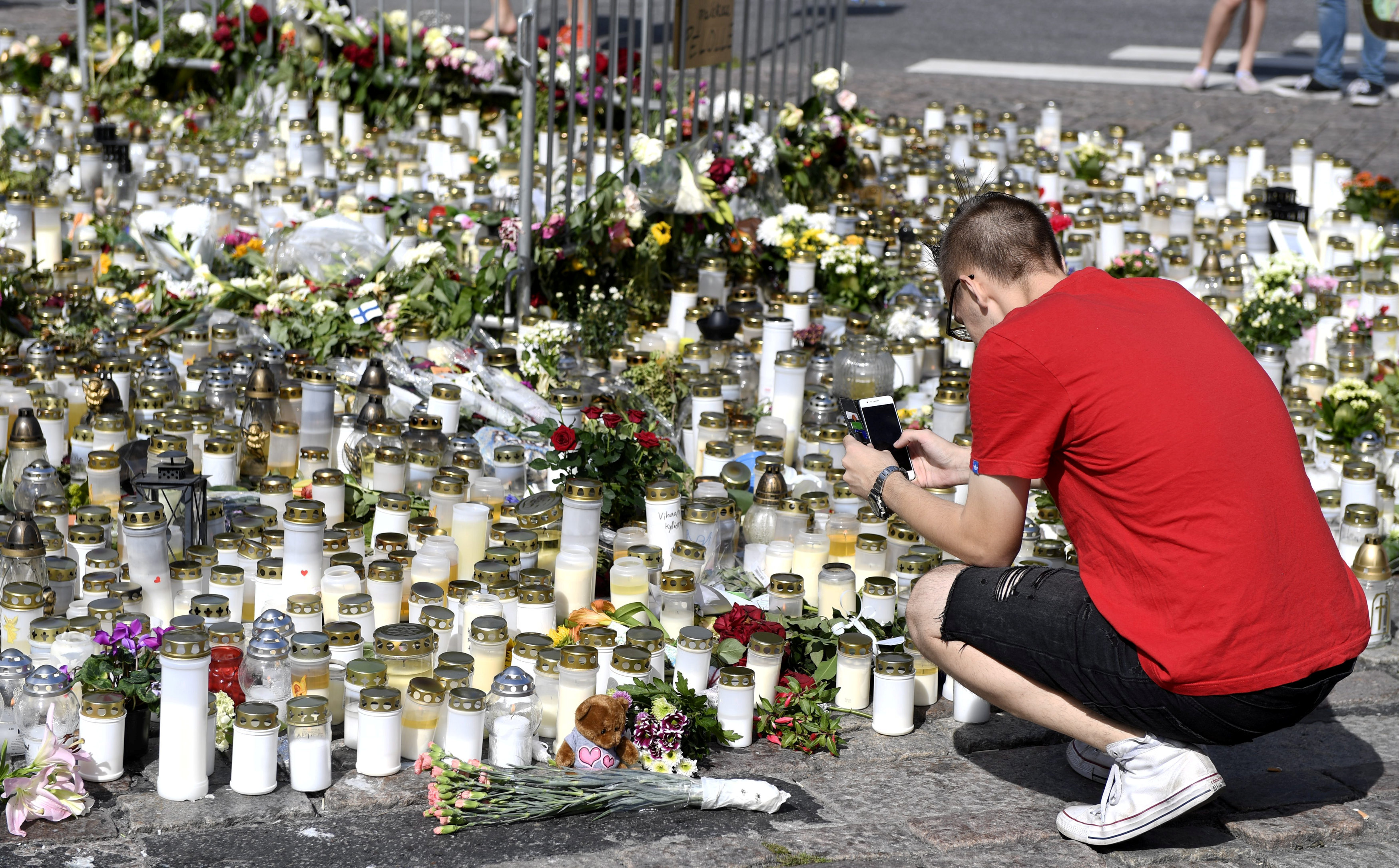 Mourners bring memorial cards, candles and flowers to the Turku Market Square, in Turku, Finland on August 20, 2017. (Lehtikuva/Vesa Moilanen/via REUTERS)