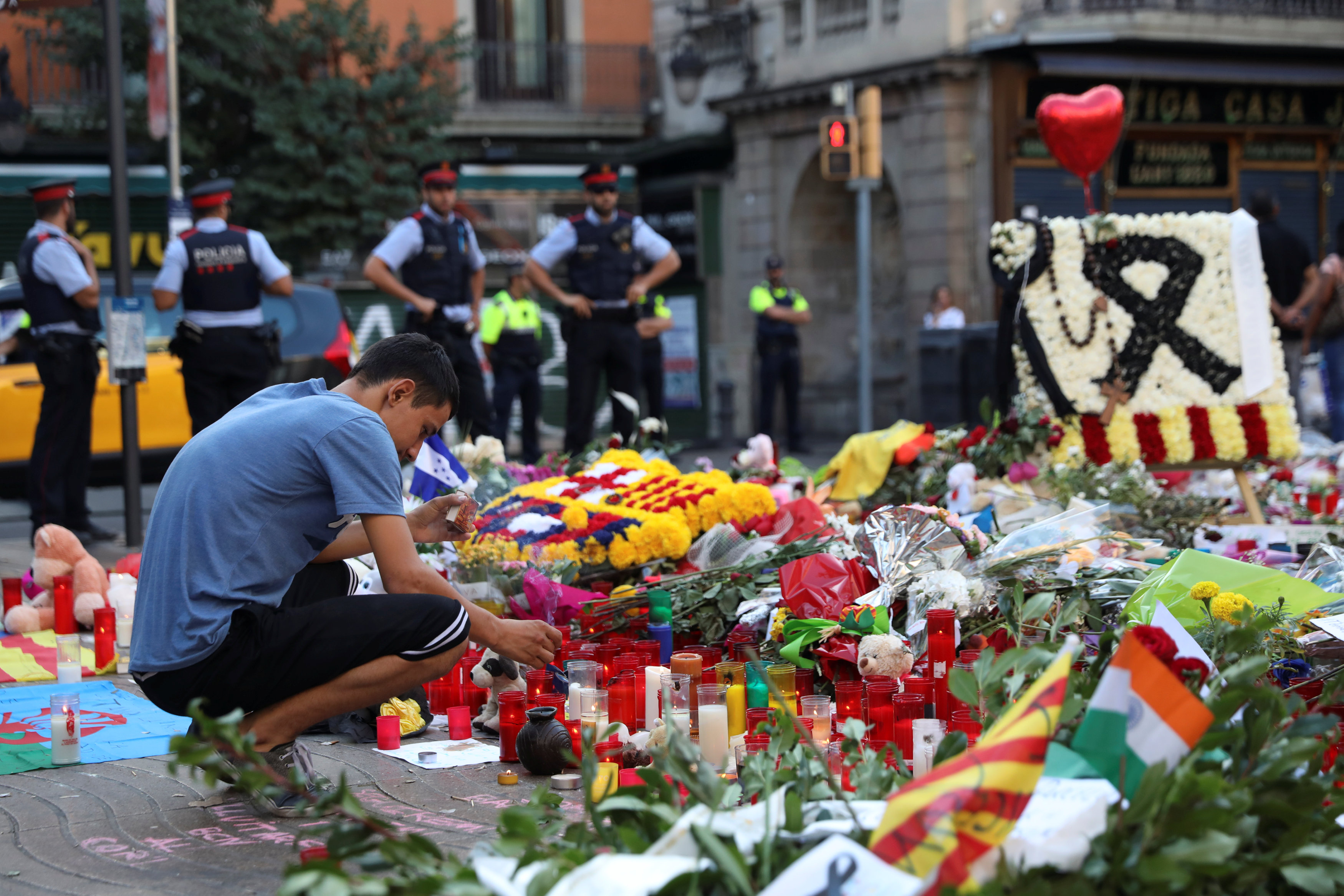 A man lights a candle at an impromptu memorial where a van crashed into pedestrians at Las Ramblas in Barcelona, Spain on August 21, 2017. (REUTERS/Susana Vera)