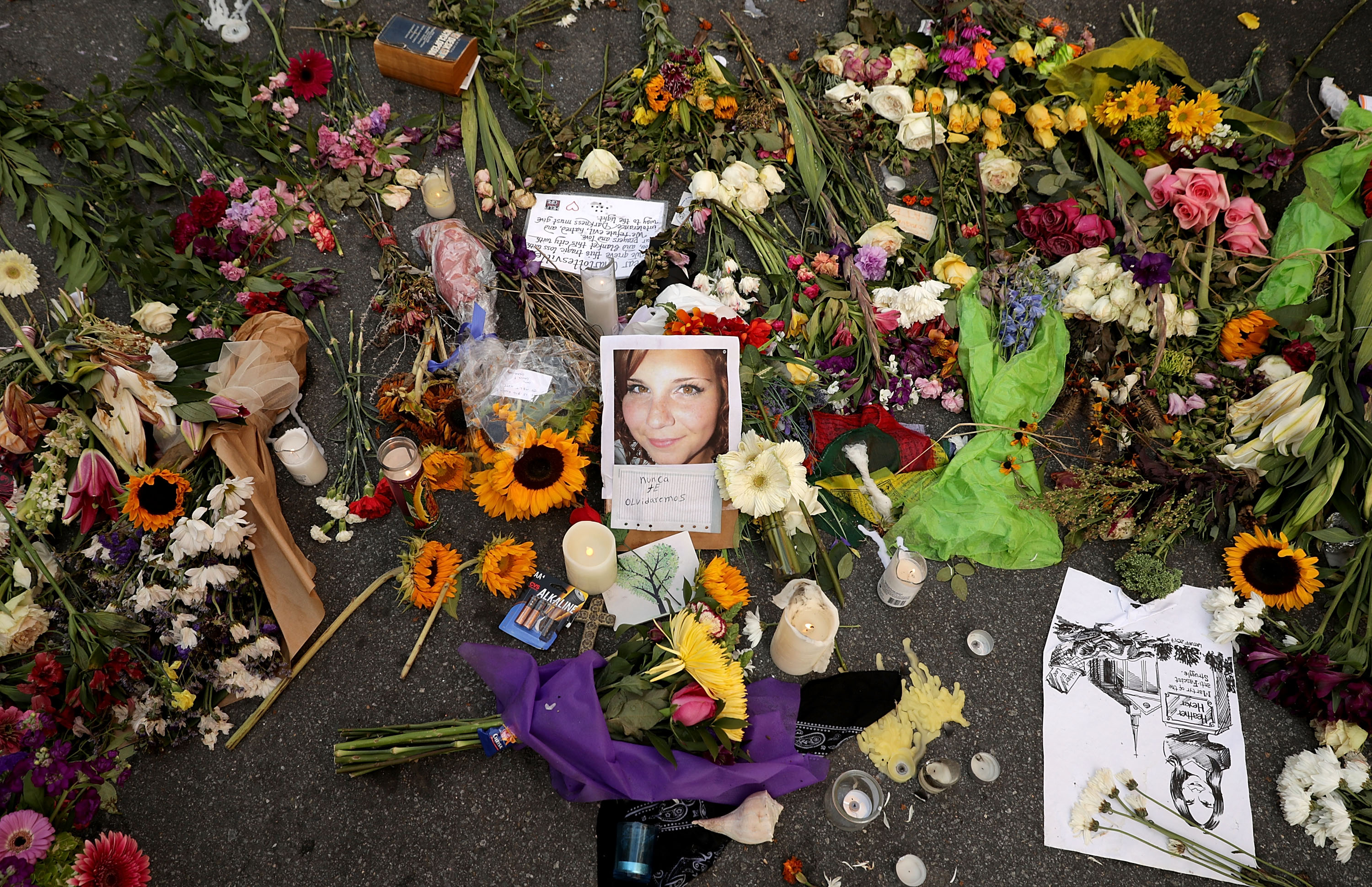Flowers, candles, and chalk-written messages surround a photograph of Heather Heyer on the spot where she was killed and 19 others injured when a car slammed into a crowd of people protesting against a white supremacist rally in Charlottesville, Virginia on Aug. 16, 2017. (Chip Somodevilla/Getty Images)
