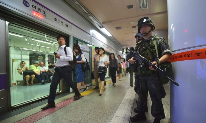 South Korean soldiers (R) stand guard as passengers walk past, during an anti-terror drill on the sidelines of South Korea-US joint military exercise, called Ulchi Freedom, at a subway station in Seoul on August 23, 2016. South Korea and the United States kicked off large-scale military exercises on August 22, triggering condemnation and threats of a pre-emptive nuclear strike from North Korea. / AFP / JUNG YEON-JE        (Photo credit should read JUNG YEON-JE/AFP/Getty Images)