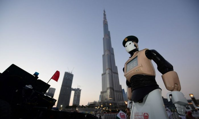 The world's first operational police robot stands at attention as they prepare a military cannon to fire to mark sunset and the end of the fasting day for Muslims observing Ramadan, in Downtown Dubai on May 31, 2017. (GIUSEPPE CACACE/AFP/Getty Images)