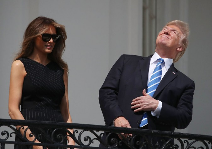 """WASHINGTON, DC - AUGUST 21:  (AFP OUT) U.S. President Donald Trump looks up toward the Solar Eclipse while joined by his wife first lady Melania Trump on the Truman Balcony at the White House on August 21, 2017 in Washington, DC. Millions of people have flocked to areas of the U.S. that are in the """"path of totality"""" in order to experience a total solar eclipse.  (Photo by Mark Wilson/Getty Images)"""