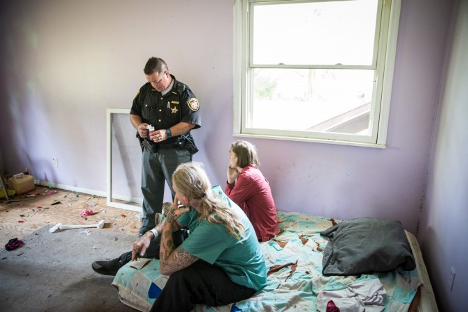 Montgomery County Deputy Sheriff Andy Teague, speaks with two people who had allegedly been using drugs inside an abandoned home in the Drexel neighborhood of Dayton, Ohio, on Aug. 3, 2017. (Benjamin Chasteen/The Epoch Times)