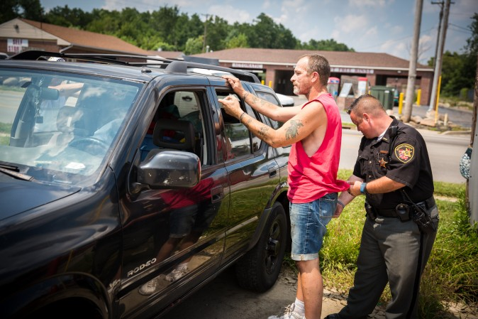 A man is searched by Montgomery County Deputy Sheriff Andy Teague for any drugs or paraphernalia in the Drexel neighborhood of Dayton, Ohio, on Aug. 3, 2017. (Benjamin Chasteen/The Epoch Times)