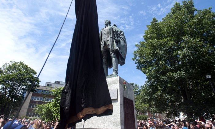 A statue of Edward Cornwallis is about to be covered as activists protest in Cornwallis Park in Halifax on July 15, 2017. The protesters, who had pledged to topple the statue of Halifax's founder, claimed victory after it was covered in a tarp. (THE CANADIAN PRESS/Darren Calabrese)