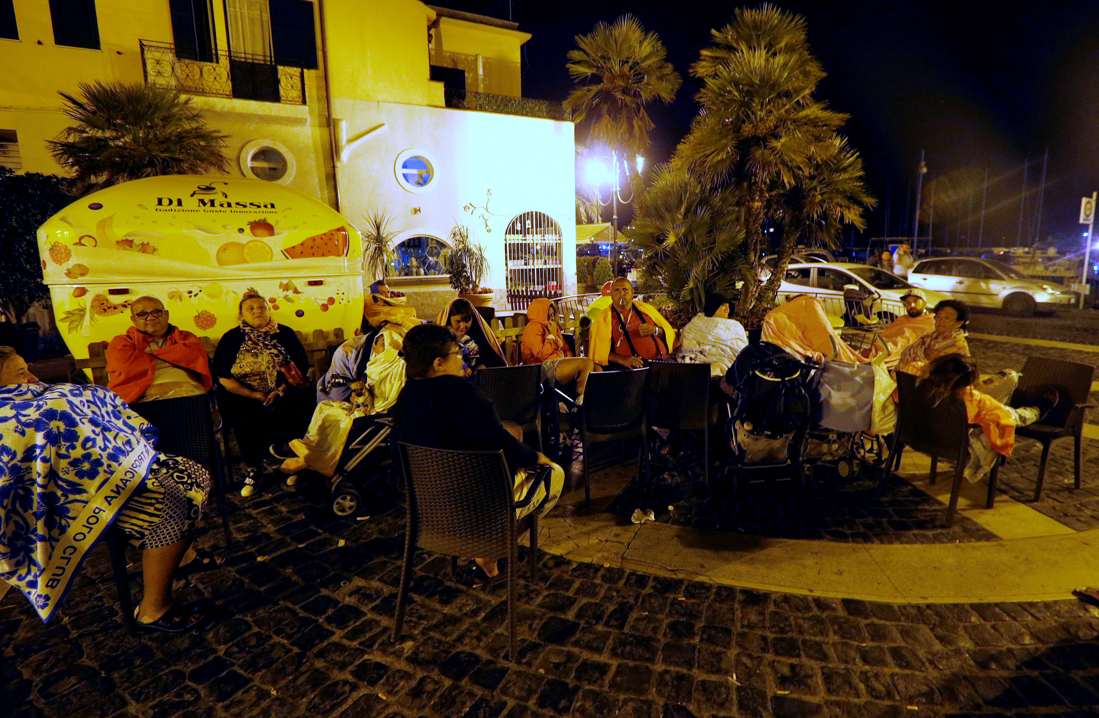 People sit in the street on early morning after an earthquake hit the island of Ischia, off the coast of Naples, Italy on August 22, 2017. (REUTERS/Ciro De Luca)