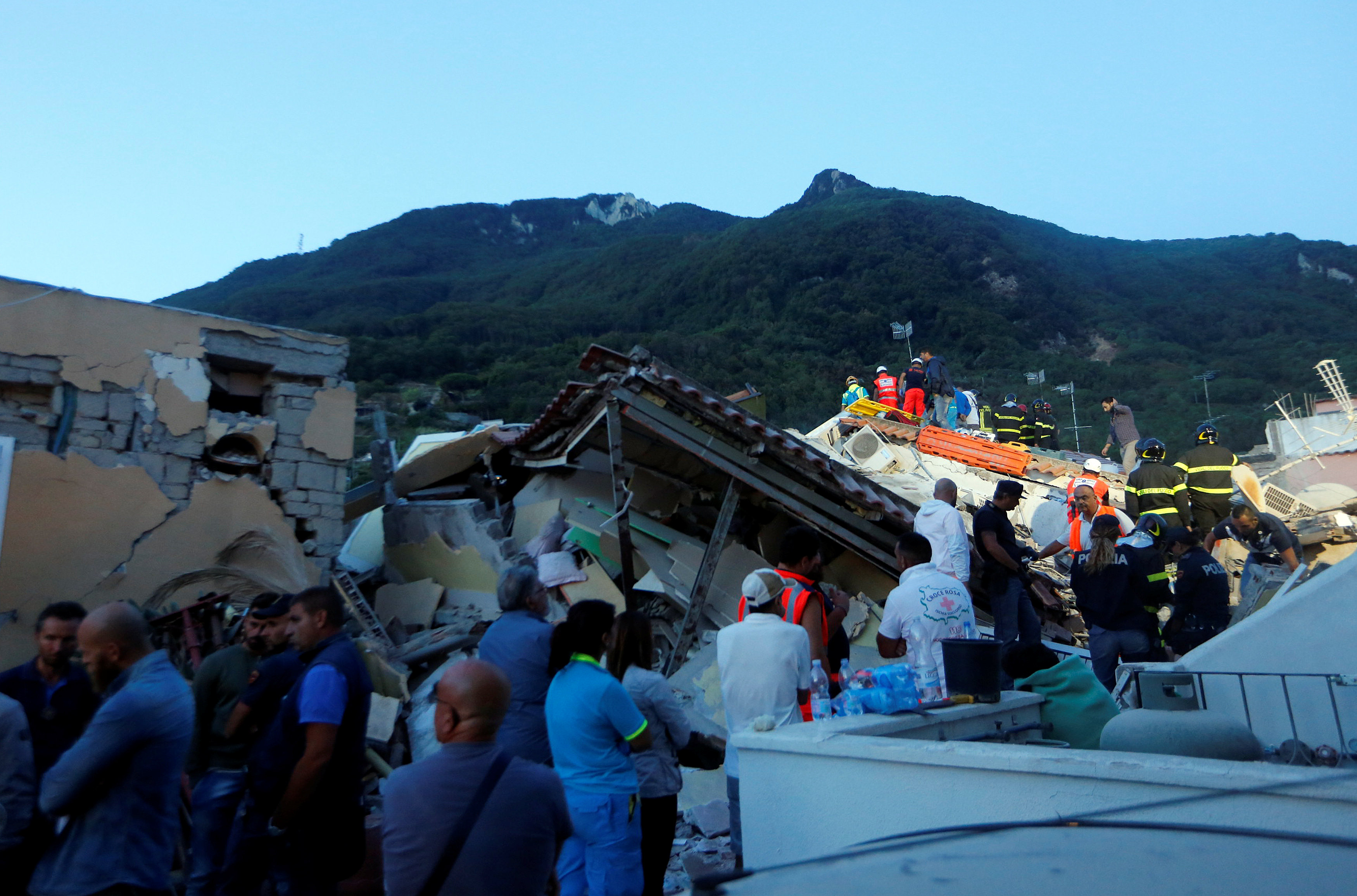 Rescue workers check a collapsed house after an earthquake hit the island of Ischia, off the coast of Naples, Italy on August 22, 2017. (REUTERS/Ciro De Luca)