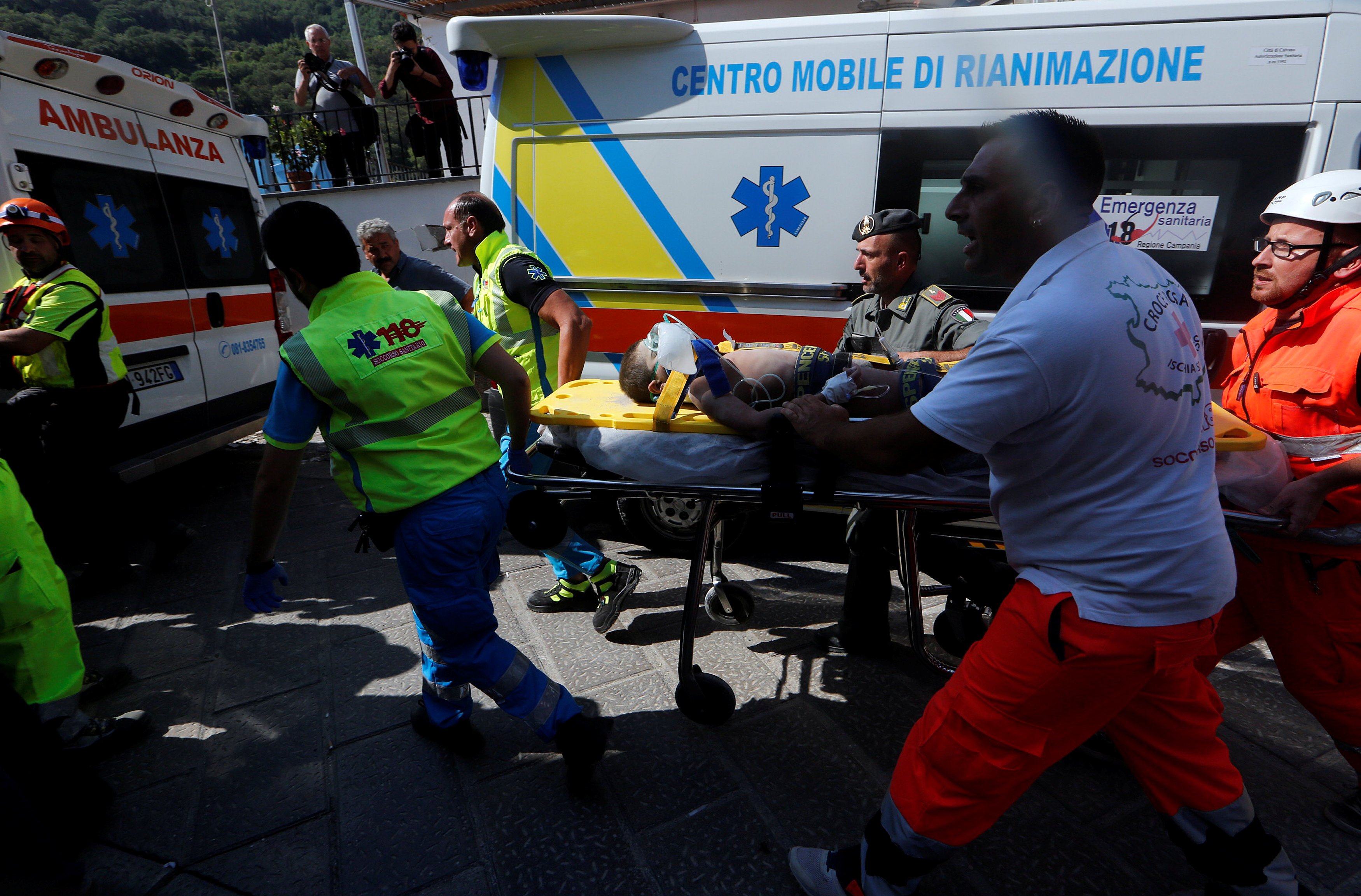 Rescue workers carry a child after an earthquake hit the island of Ischia, in Naples, Italy on August 22, 2017. (REUTERS/Ciro De Luca)