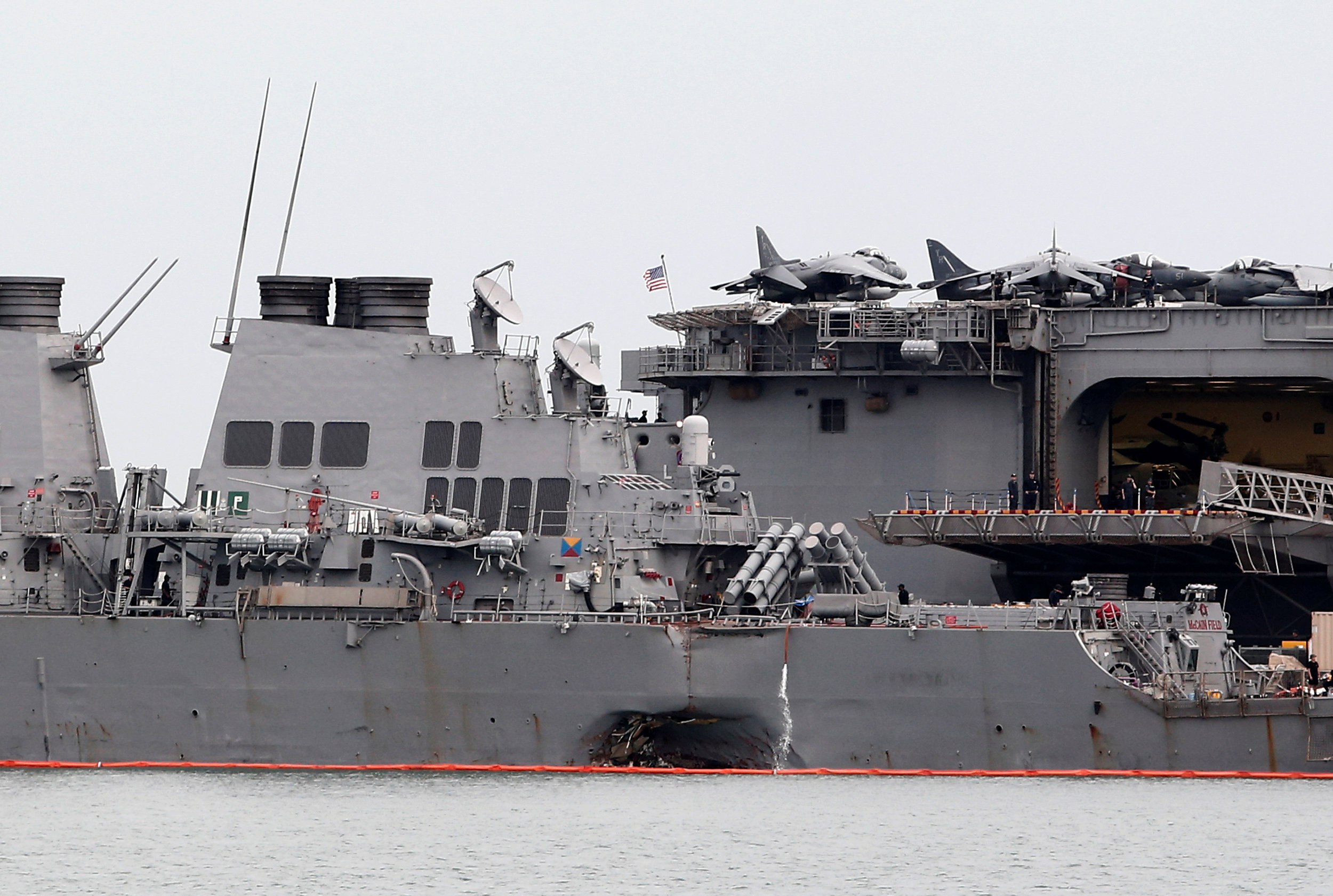 The damaged USS John McCain is docked next to USS America at Changi Naval Base in Singapore on August 22, 2017. (REUTERS/Calvin Wong)