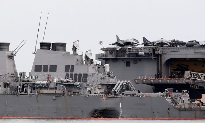 The damaged USS John McCain is docked next to USS America at Changi Naval Base in Singapore August 22, 2017. (Reuters/Calvin Wong)
