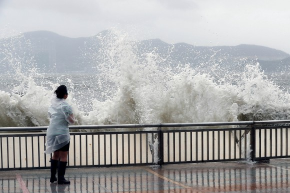 A woman stands beside a big wave on a waterfront Typhoon Hato hitting in Hong Kong, China August 23, 2017. (Reuters/Tyrone Siu)