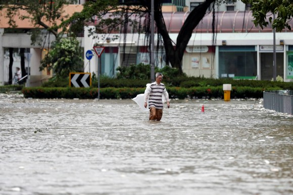 A man walks through a flooded street as Typhoon Hato hits Hong Kong, China August 23, 2017. (Reuters/Tyrone Siu)