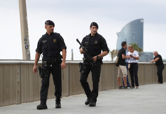FILE PHOTO: Armed Catalan Mossos d'Esquadra officers patrol along La Barceloneta beach in Barcelona, Spain, August 19, 2017. (Reuters/Sergio Perez)