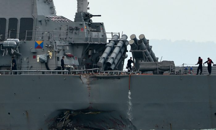 The guided-missile destroyer USS John S. McCain is seen with a hole on its portside after a collision with an oil tanker outside Changi naval base in Singapore on Aug. 21, 2017. An admiral in the PLA Navy celebrated the collision, which involved loss of American life. (ROSLAN RAHMAN/AFP/Getty Images)