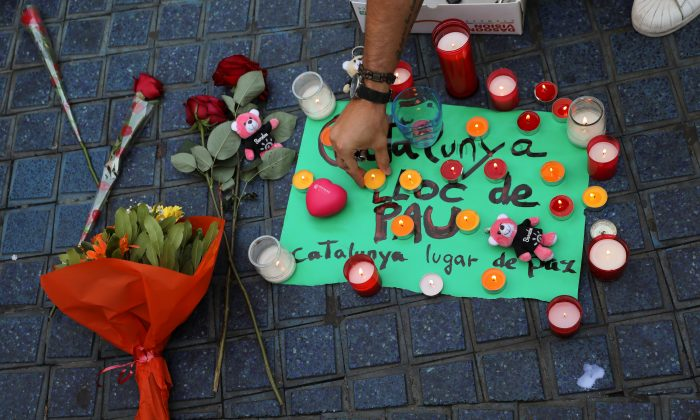 """A person places a candle on a placard, reading in Spanish and Catalan """"Catalonia, place of peace"""", in the area where a van crashed into pedestrians at Las Ramblas street in Barcelona, Spain on August 18, 2017. (REUTERS/Sergio Perez)"""