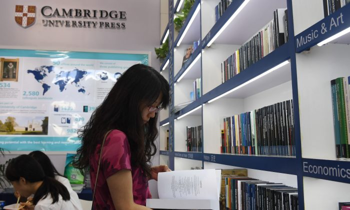 A woman reads a book at the Cambridge University Press stand at the Beijing International Book Fair in Beijing on Aug. 23, 2017.  Just days after an outcry over an attempt to censor a British academic journal in China, hundreds of international publishing houses are courting importers at a major book fair in Beijing. / AFP PHOTO / Greg Baker / TO GO WITH China-Britain-US-censorship-education, FOCUS by Joanna CHIU        (Photo credit should read GREG BAKER/AFP/Getty Images)