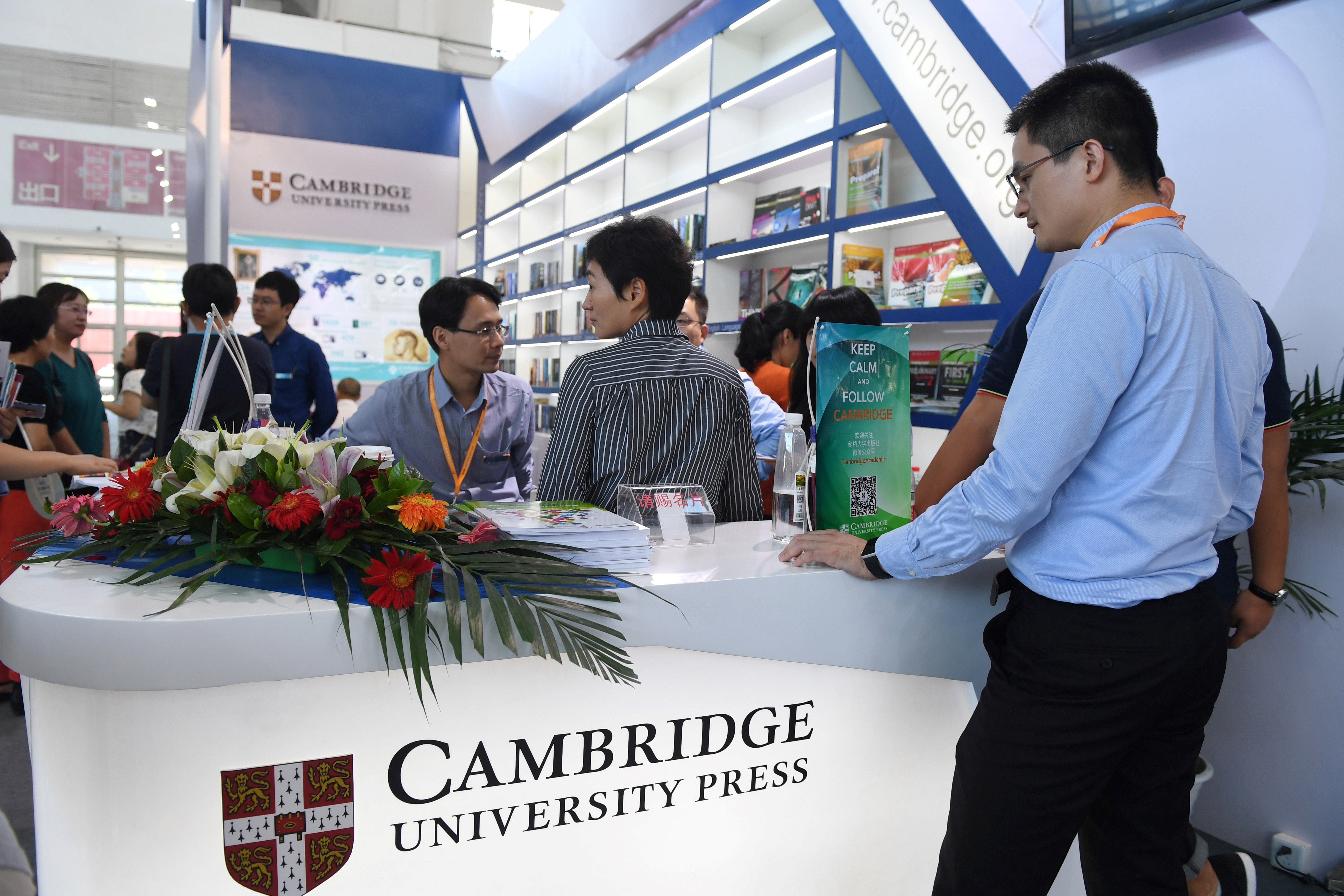 People at the Cambridge University Press at the Beijing International Book Fair in Beijing on Aug. 23, 2017. Just days after an outcry over an attempt to censor a British academic journal in China, hundreds of international publishing houses are courting importers at a major book fair in Beijing. (GREG BAKER/AFP/Getty Images)