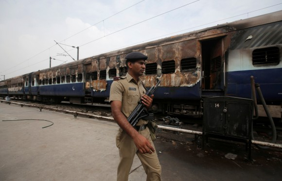 A security personnel member walks past a burnt carriage of a train near a railway station in New Delhi, India, August 26, 2017. (Reuters/Adnan Abidi)