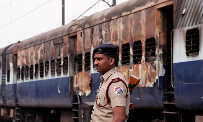 A security personnel member stands guard outside a burnt carriage of a train near a railway station in New Delhi, India, August 26, 2017. (Reuters/Adnan Abidi)