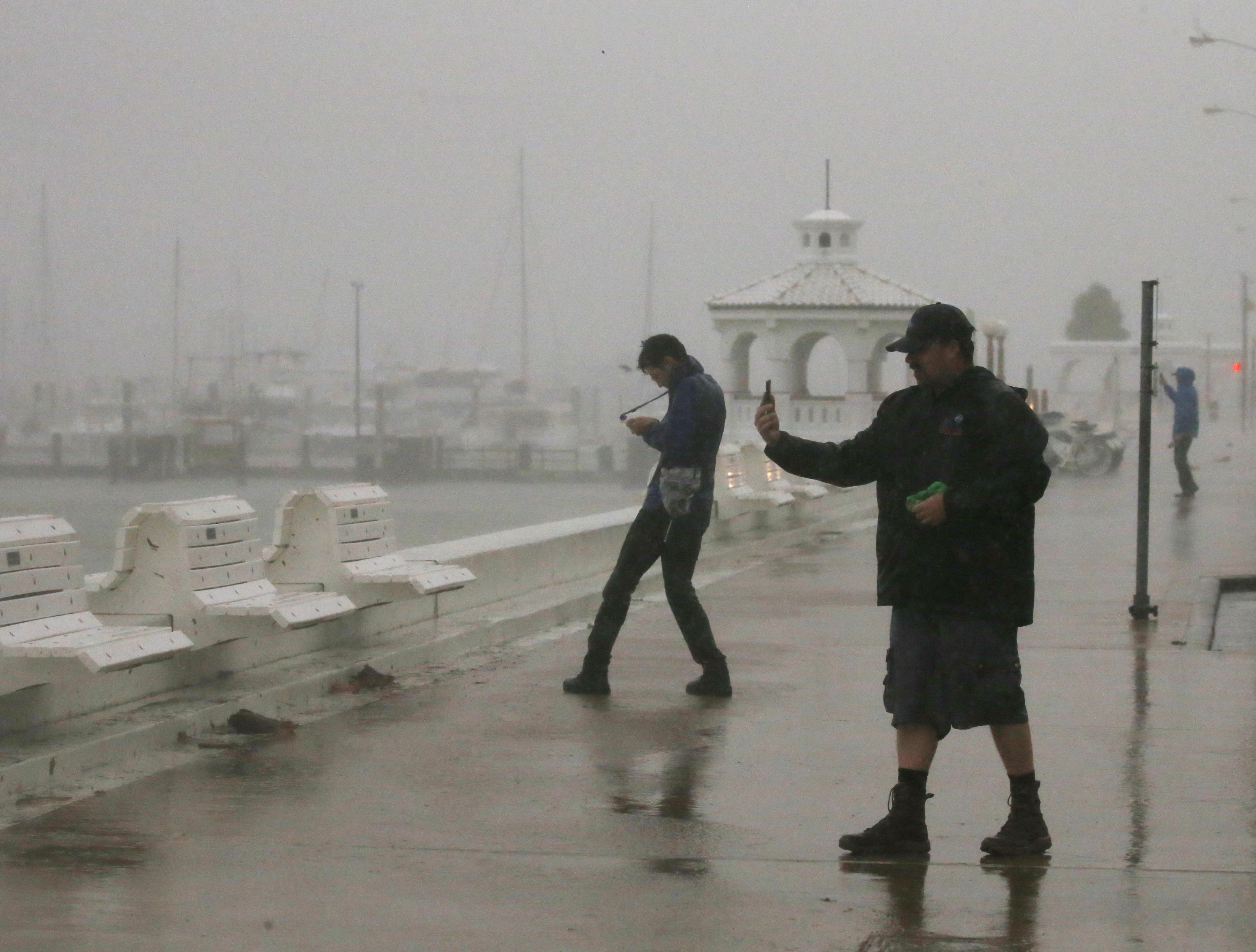 A storm chaser films himself on a camera phone as Hurricane Harvey approaches, on the boardwalk in Corpus Christi, Texas. (REUTERS/Adrees Latif)