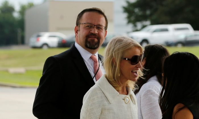 Then-White House adviser Sebastian Gorka (L), standing with White House counselor Kellyanne Conway (C), waits for U.S. President Donald Trump to arrive to board Air Force One for travel to Ohio from Joint Base Andrews, Maryland on July 25, 2017. (REUTERS/Jonathan Ernst)