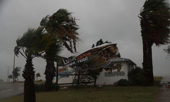 A sign blows in the wind after being partially torn from its frame by winds from Hurricane Harvey on August 25, 2017 in Corpus Christi, Texas.  (Photo by Joe Raedle/Getty Images)