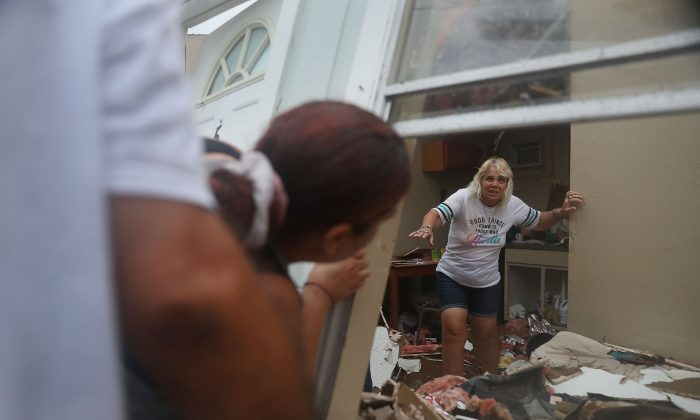 Donna Raney makes her way out of the wreckage of her home as Daisy Graham tells her she will help her out of the window after Hurricane Harvey destroyed the apartment on August 26, 2017 in Rockport, Texas. Donna was hiding in the shower after the roof blew off and the walls of her home caved in by the winds of Hurricane Harvey. (Joe Raedle/Getty Images)