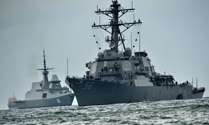 The guided-missile destroyer USS John S. McCain (R), with a hole on its portside after a collision with an oil tanker, is escorted by Singapore Navy RSS Intrepid (L) to Changi naval base in Singapore on August 21, 2017. Ten US sailors were missing and five injured after their destroyer collided with a tanker east of Singapore on Aug. 20, the second accident involving an American warship in two months. (ROSLAN RAHMAN/AFP/Getty Images)