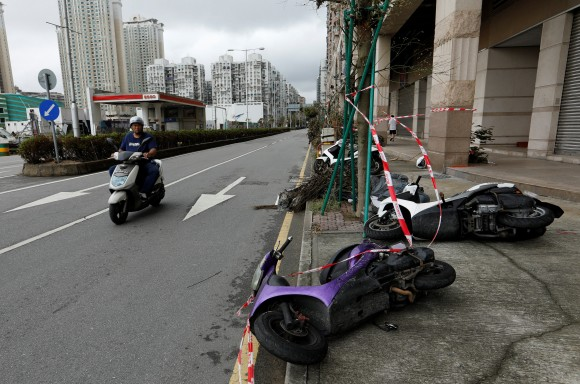 A man looks at motorcycles tipped over by strong wind from tropical storm Pakhar in Macau, China August 27, 2017. (Reuters/Tyrone Siu)