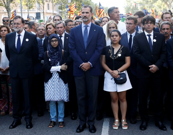 Spain's King Felipe (C), Prime Minister Mariano Rajoy (L) and Catalan regional president Carles Puigdemont (R) take part in a march of unity after the attacks last week, in Barcelona, Spain on Aug. 26, 2017. (REUTERS/Juan Medina)
