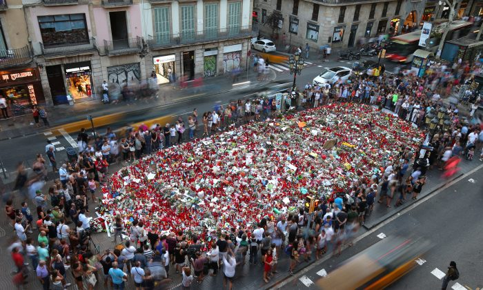 People gather at an impromptu memorial where a van crashed into pedestrians at Las Ramblas in Barcelona, Spain on Aug. 24, 2017. (REUTERS/Albert Gea)
