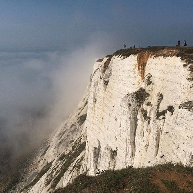 People stand on a cliff at Beachy Head amidst mist, near Eastbourne, Britain on Aug. 27, 2017. (Louisa Neale via REUTERS)