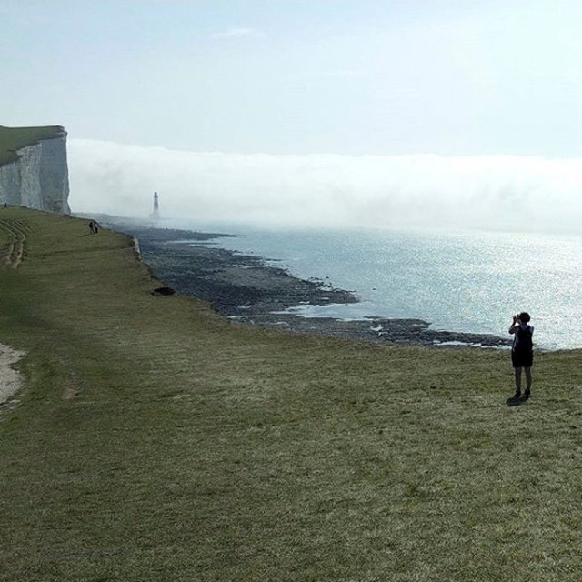 A person takes photo of the mist near Beachy Head Lighhouse, near Eastbourne, Britain on Aug. 27, 2017. (Nick Harrison Neale via REUTERS)