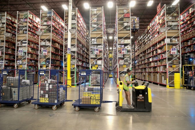 A Worker packs and ships customer orders at the 750,000-square-foot Amazon fulfillment center in Romeoville, Ill., on Aug. 1. (Scott Olson/Getty Images)