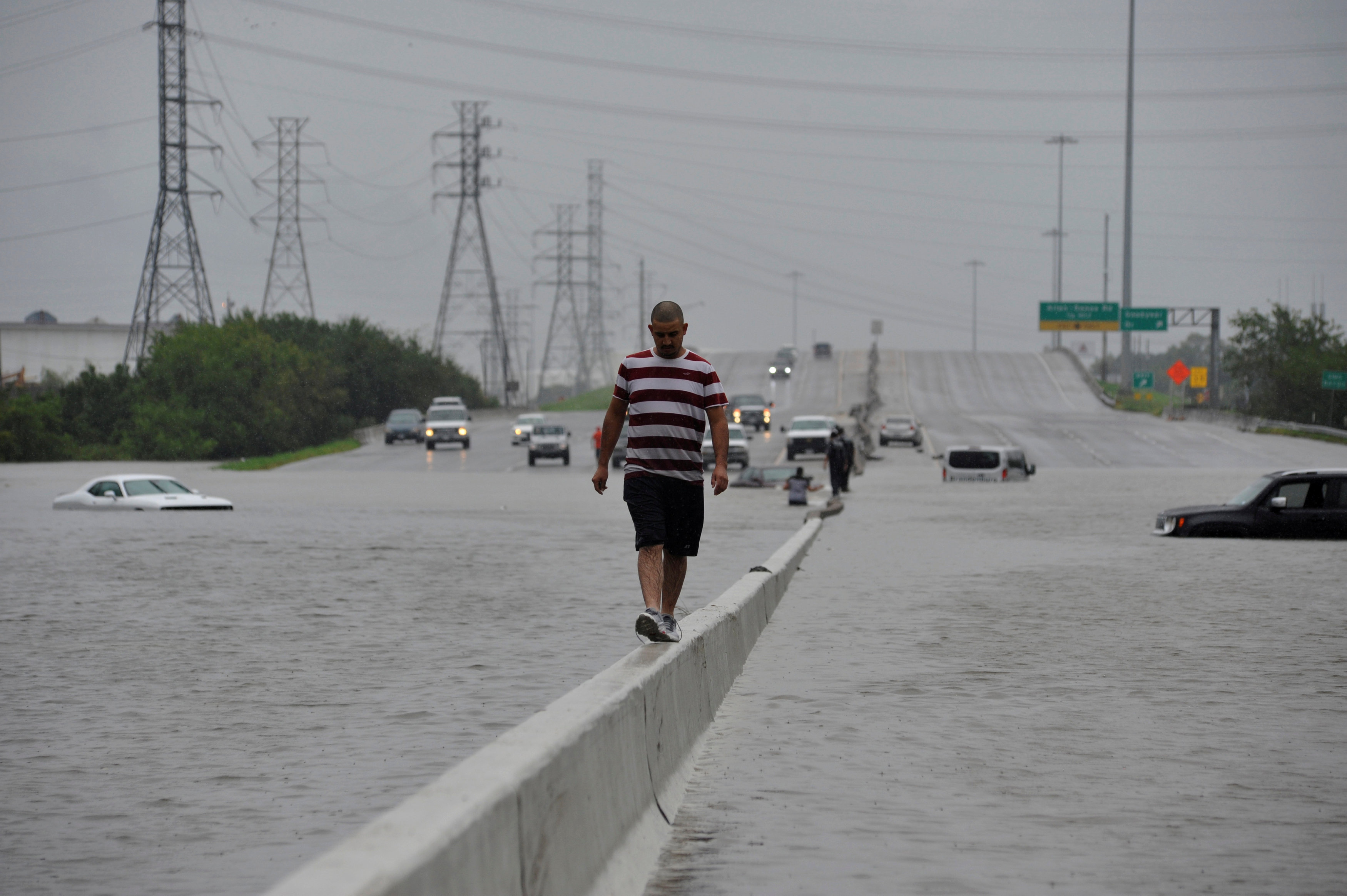 A stranded motorist escapes floodwaters on Interstate 225 after Hurricane Harvey inundated the Texas Gulf coast with rain causing mass flooding, in Houston, Texas, U.S. on Aug. 27, 2017.  (REUTERS/Nick Oxford)